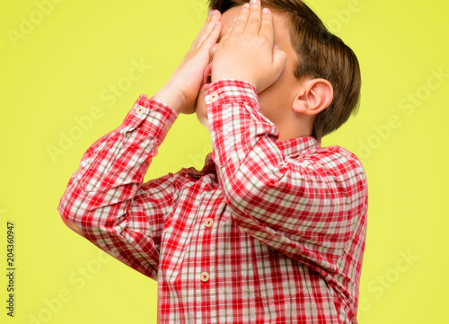 Handsome toddler child with green eyes stressful keeping hands on head, tired and frustrated over yellow background
