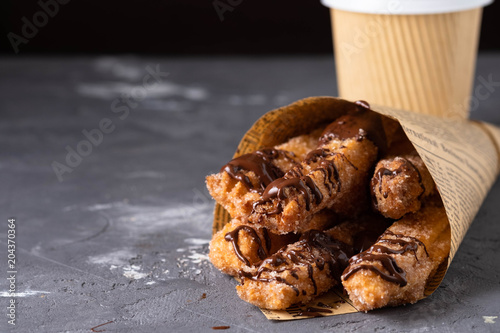 Poster Freshly fried churros (traditional spanish dessert) with hot chocolate and coffee to go in paper bag. Street food concept