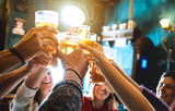 Group of happy friends drinking and toasting beer at brewery bar restaurant - Friendship concept with young people having fun together at cool vintage pub - Focus on middle pint glass - High iso image - 204371159