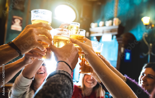Leinwandbild Motiv Group of happy friends drinking and toasting beer at brewery bar restaurant - Friendship concept with young people having fun together at cool vintage pub - Focus on middle pint glass - High iso image