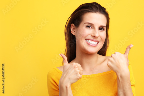Woman against yellow wall background