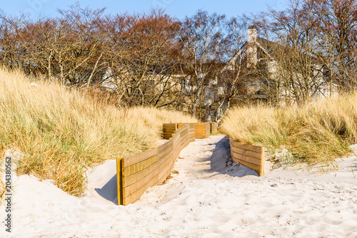 Fototapeta Falsterbo, Sweden - Sand is slowly reclaiming the walled in path to the beach.