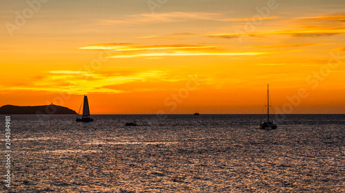 Plexiglas Zee zonsondergang sunset on ibiza island with sailboats in the background