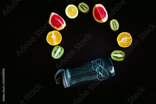 Fitness bottle of water and different fruits on black table. Background layout with free text space.