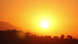 Time lapse of the sun rising behind low mountains - 204390792