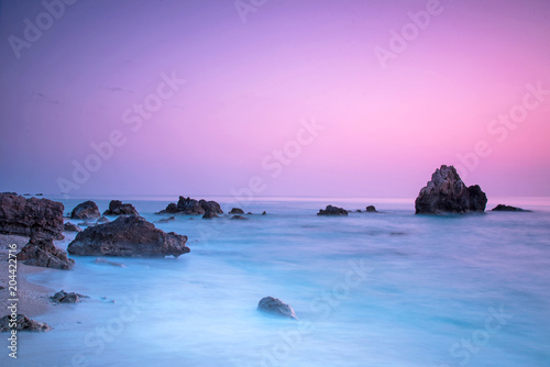 Plexiglas Purper A picturesque magical mystical beautiful scenery with waves and stones in the middle of the sea on the coast at sunset. (meditation, antistress, relaxation - concept)