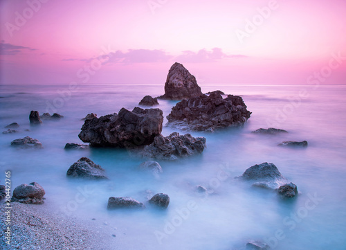 Fotobehang Purper A picturesque magical mystical beautiful scenery with waves and stones in the middle of the sea on the coast at sunset. (meditation, antistress, relaxation - concept)