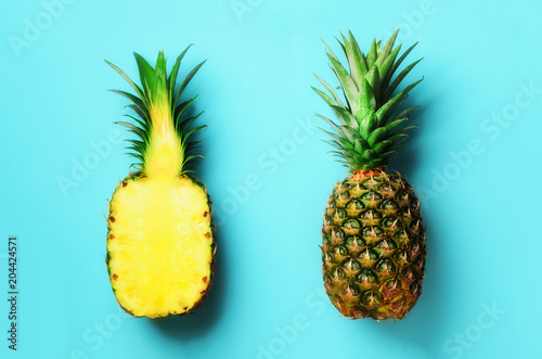 Whole pineapple and half sliced fruit on blue background. Top View. Copy Space. Bright pineapples pattern for minimal style. Pop art design, creative concept - 204424571
