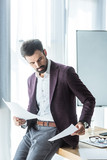 handsome young businessman doing paperwork while leaning back on desk at office - 204470998