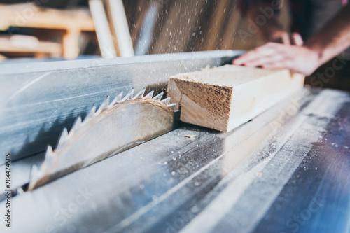 Carpenter using circular saw in workshop - 204474585