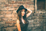 Young fashion woman with hat stand in front old abandoned house summer day - 204475593
