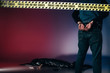 Quadro Rear view of murderer in cuffs behind police line on dark background