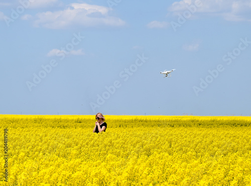Fotobehang Geel Dron flies after the girl. Shooting with a drone in the field. A girl in a black dress in a field of flowering rape