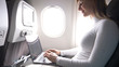 CLOSE UP: Happy businesswoman is typing on her high tech laptop during flight.