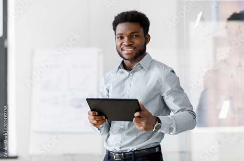 business, people and technology concept - african american businessman with tablet pc computer at office