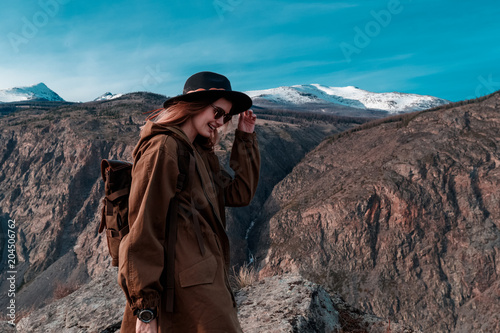 Fotobehang Cappuccino Beautiful young woman with retro backpack on the top of cliff amazing mountain range landscape. Sunset. Hipster. Adventure. Travel lifestyle. Copy space.