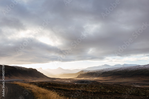 Fotobehang Donkergrijs Mountain road leading to the peaks in Iceland.
