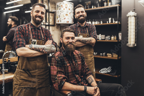 Fototapeta Hipster young good looking man visiting hairstylist and barber in barber shop.