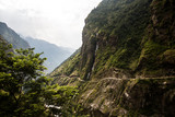 Scenic Himalayan Landscape. View of Waterfall, Mountains and the road with forest and green trees. Annapurna Range on Annapurna Circuit Trek. Autumn season in Nepal, Asia.