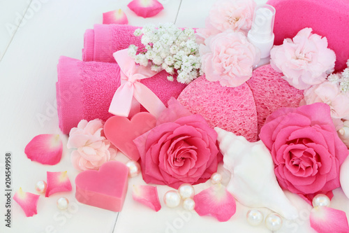 Plexiglas Spa Bathroom beauty cleansing products with pink roses and carnation flowers, shell and heart shaped soap, body lotion, sponges, wash cloth and decorative pearls on white wood background.