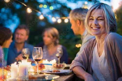 Group of friends gathered around a table in a garden on a summer evening to share a meal and have a good time together. Focus on a beautiful woman
