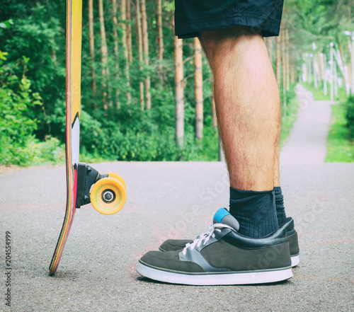 Plexiglas Skateboard Side view of guy staying with and longboard or skateboard on asphalt road. Bottom view of legs of young active man