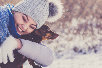 Woman playing with dog during winter