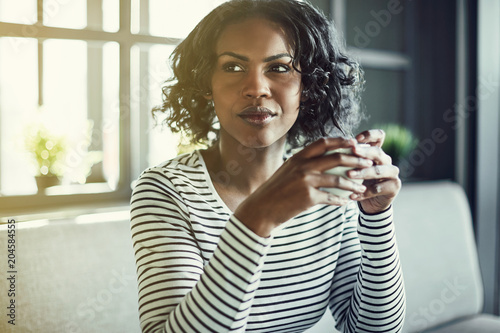 Fototapeta Young African woman sitting in a cafe drinking coffee