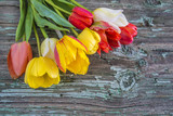 Bouquet of multicolored tulips on rustic wooden background - 204597706