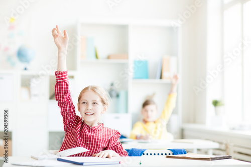 Successful girl raising her hand at lesson to voice her ideas to teacher and classmate