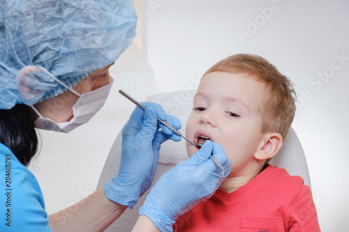Fototapeta Dentist medical examination of child patient teeth using a mirror of instrument Caries, tooth damage, illness.
