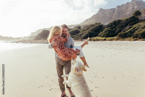 Fototapeta Romantic mature couple with a dog on the beach