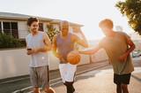Basketball guys walking on street playing with the ball