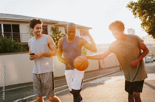 Plexiglas Basketbal Basketball guys walking on street playing with the ball