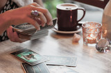 Woman is reading Tarot cards in cafe - 204618946
