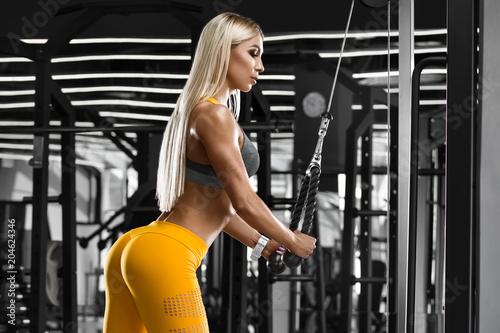 Seksowny sportowy dziewczyna trening w gym. Sprawności fizycznej kobieta robi ćwiczeniu. Seksowne pośladki w leginsach