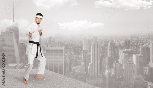 Fototapeta Young karate trainer doing karate tricks on the top of a metropolitan city