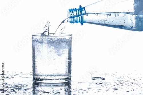 Fototapeta samoprzylepna Mineralwasser in ein Glas eingeschenkt, Hintergrund weiß