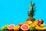 Summer background with fruit, tropical fresh fruits, juicy oranges, sliced mandarin, grapefruit and pineapple on blue background - 204635591