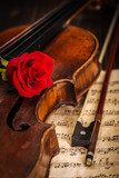 Old violin and bow with red rose