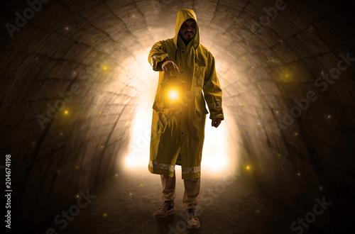 Brzydki mężczyzna chodzi w deszczowu z rozjarzonym lampionem w ciemnym tunelu