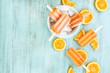 Orange Popsicles In White Bowl with Sliced Fruit