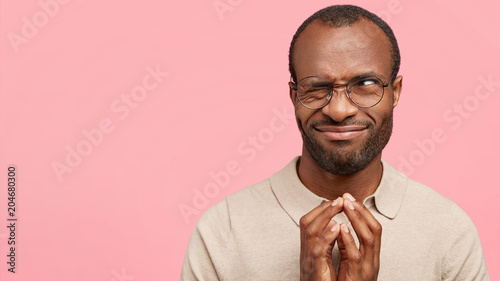 Horizontal portrait of handsome funny male with dark healthy skin, looks with intriguing expression aside, isolated over pink background. Hesitant black young man feels doubt about something © Wayhome Studio