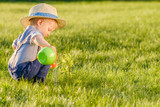 Toddler child outdoors. One year old baby boy wearing straw hat using watering can - 204684173