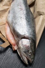 Close up shot of raw fresh rainbow trout on a black background on paper bag Preparations for cooking