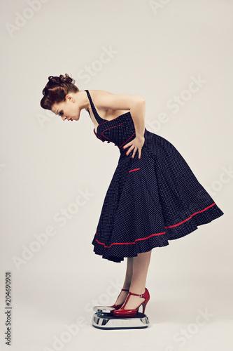 femme pin-up se pesant sur une balance