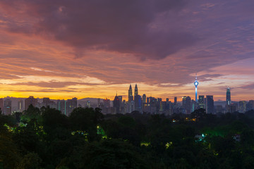 Majestic sunrise over Petronas Twin Towers and surrounded buildings in downtown Kuala Lumpur, Malaysia.