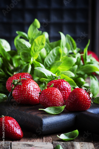 Strawberries and green basil, vintage wooden background, selective focus