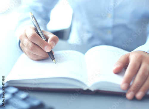 Female hand holding pen ready to make note in opened notebook sheet. - 204719301