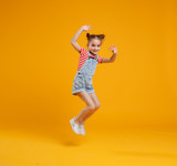 funny child girl jumping on colored yellow background - 204726164